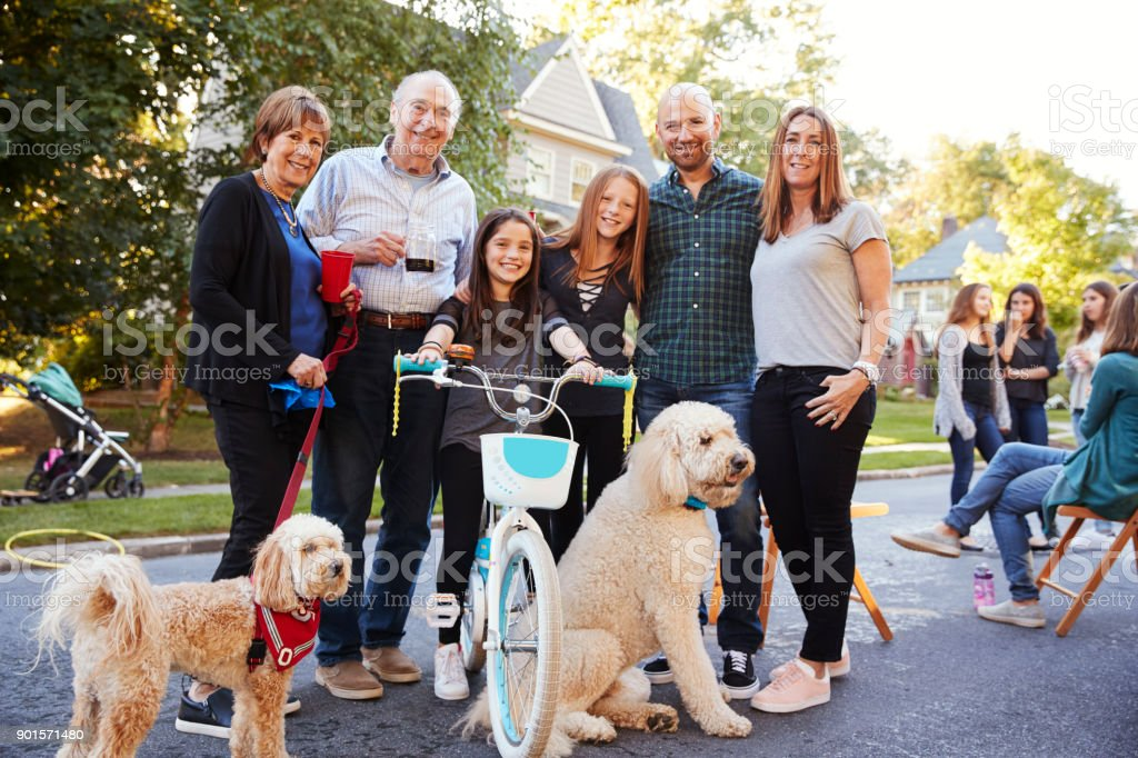 Neighbours with pet dogs smiling to camera at a block party stock photo