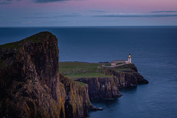 Neist Point, famous landmark with lighthouse on Isle of Skye, Scotland at blue hour. stock photo