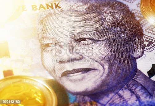 Face of Nelson Mandela on a large-denomination South African banknote wth Five Rand coin alongside.