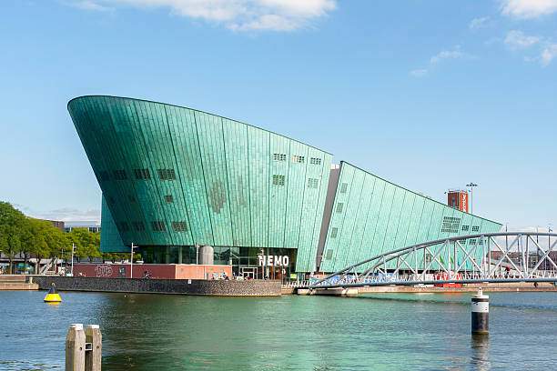 Nemo Museum Amsterdam, the Netherlands - June 16, 2015: the  modern building of Science Center Nemo. The museum is located at the Oosterdok in Amsterdam-Centrum, situated between the Oosterdokseiland and Kattenburg. The museum was started in 1923, and the current headquarter, designed by Renzo Piano, is occupied since 1997. nemo museum stock pictures, royalty-free photos & images