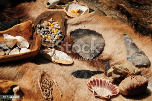 Animal skins and napped flint and other objects in a re-enactment camp.
