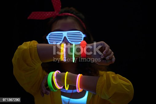 Cheerful young woman with neon bracelets in dark room
