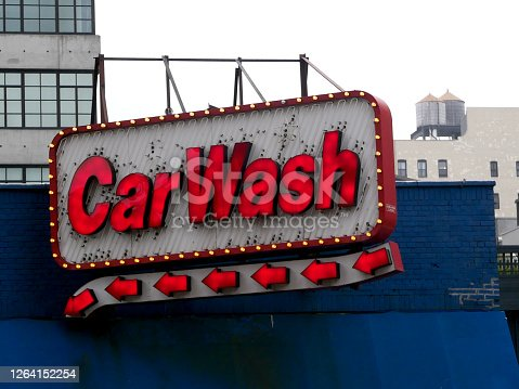 A red and white neon car wash sign hangs on a blue rooftop.