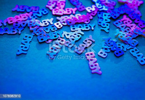 875685464istockphoto Neon coloured confetti baby on blue background 1078382910