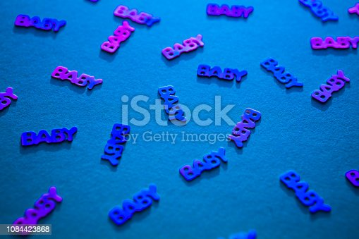 875685464istockphoto Neon coloured confetti baby on blue background 1084423868