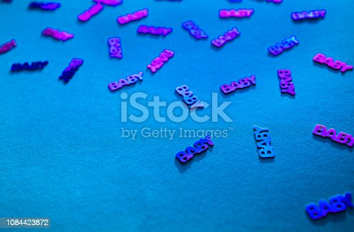 875685464istockphoto Neon coloured confetti baby on blue background 1084423872