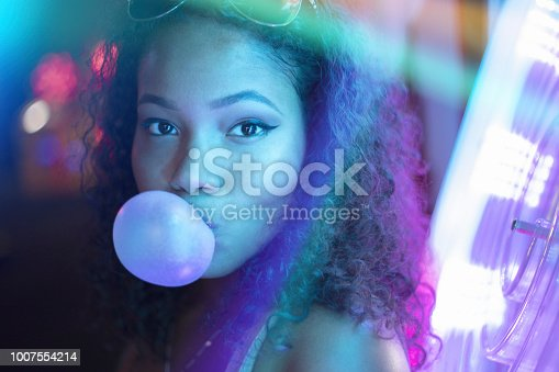 A stock photo of a young girl surrounded by neon lights and reflections. Photographed using the Canon EOS 1DX Mark II