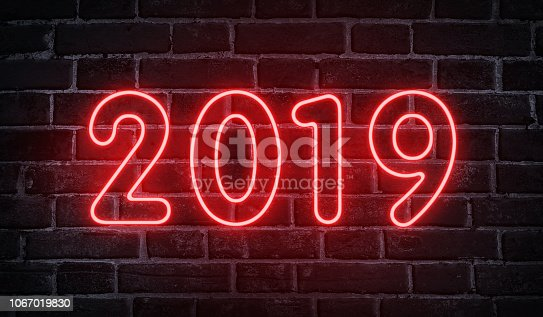 1029792184 istock photo Neon glowing 2019 new year advertising design on wall 1067019830