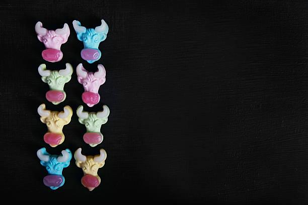 neon gummy a cow candies on the black texture background - kuhbonbon stock-fotos und bilder