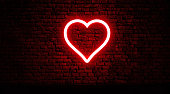 Neon heart on brick wall