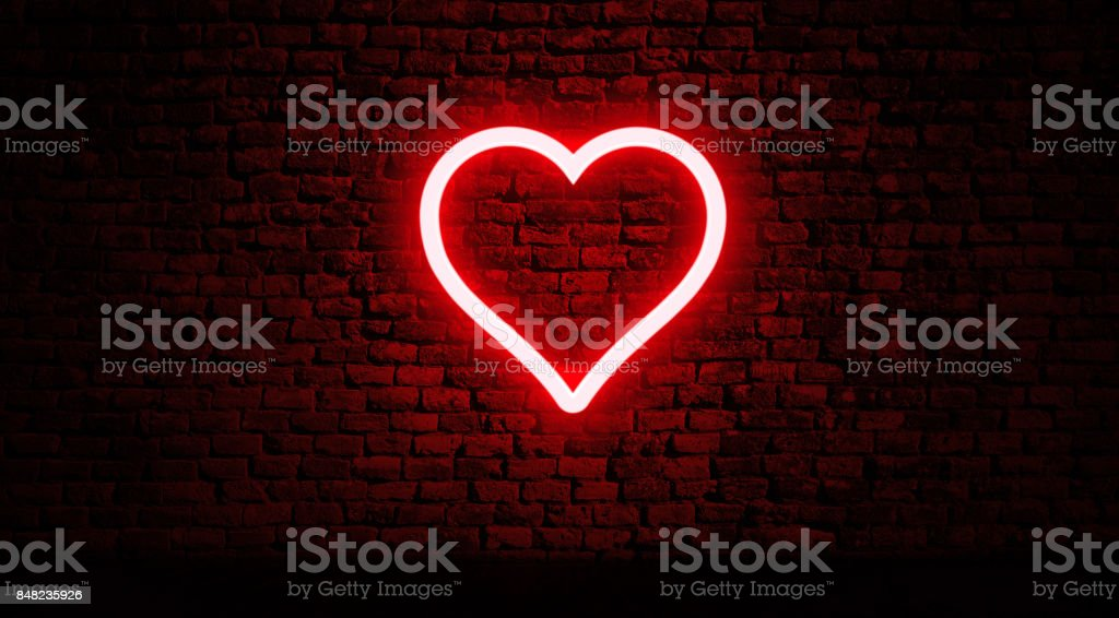 Neon heart on brick wall stock photo