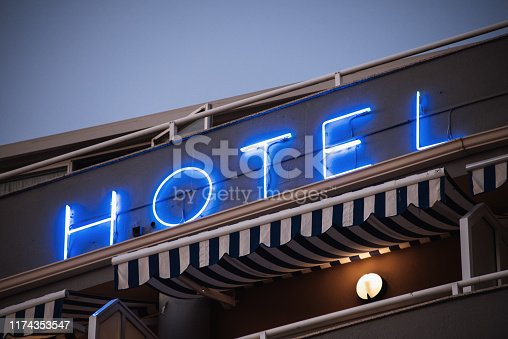 A neon hotel sign on a building