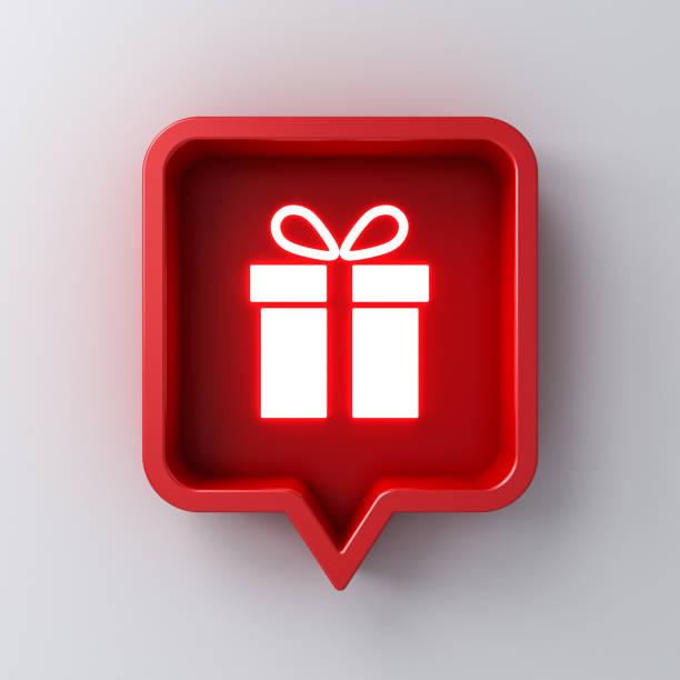 赤いソーシャルメディア通知スピーチバブルボックスピンでネオンライトギフトアイコンは、影と暗い白い壁の背景に隔離 - アイコン プレゼント ストックフォトと画像