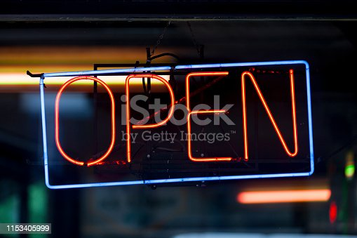Close-up on a neon light shaped into a blue rectangle and the word