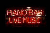 Close-up on a neon light shaped into the short phrase 'Piano Bar, Live Music'.