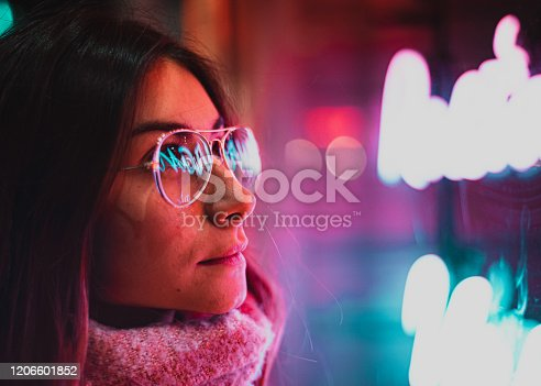 1071416330 istock photo Neon light reflected on girl's glasses 1206601852