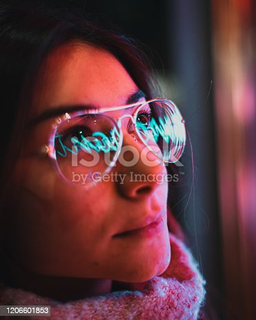 1071416330 istock photo Neon light reflected on girl's glasses 1206601853