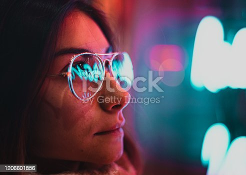 1071416330 istock photo Neon light reflected on girl's glasses 1206601856