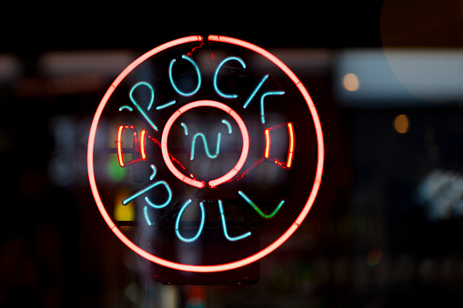 Close-up on a neon light shaped into a circle with written inside