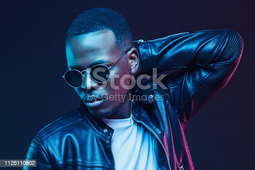 1095939686istockphoto Neon light studio portrait of african american male model wearing trendy leather jacket and sunglasses 1125110802