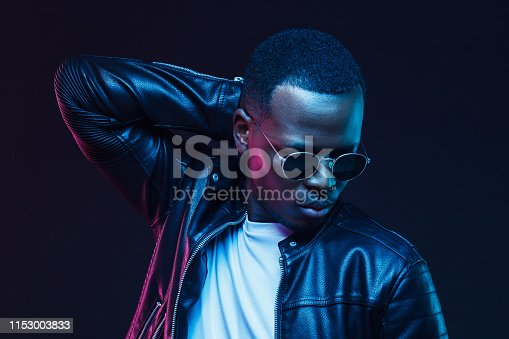 1095939686istockphoto Neon light studio portrait of handsome african american male model wearing trendy leather jacket and sunglasses 1153003833