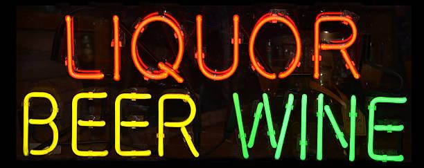 Neon lights spelling out liquor beer wine stock photo