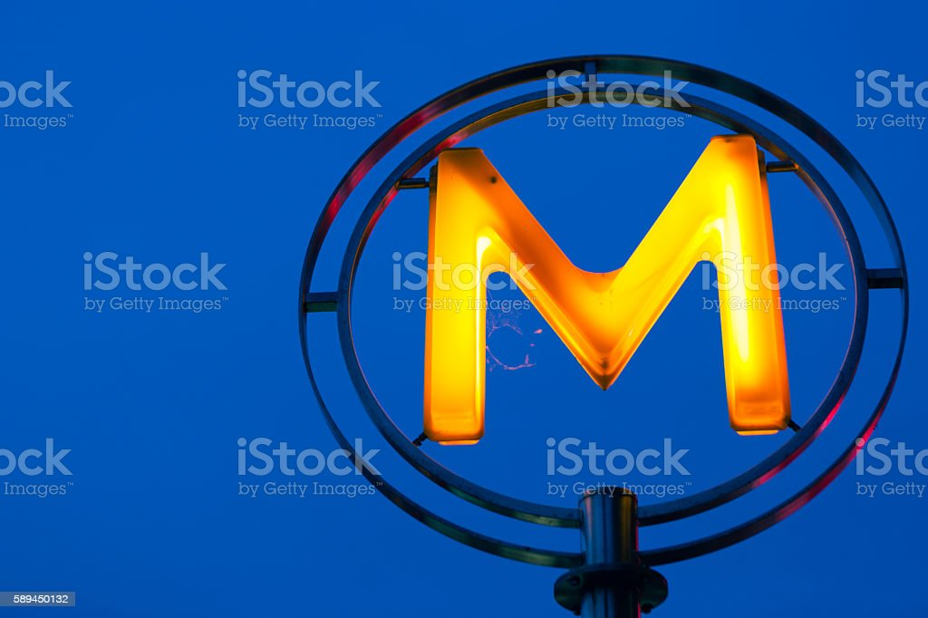 Neon M letter against blue night sky stock photo