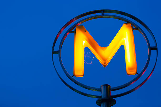 Neon M letter against blue night sky stock photo