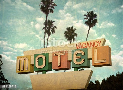 aged and worn neon motel sign with palm trees