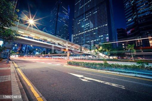 Neon night highways zooming traffic through skyscraper cityscape Hong Kong