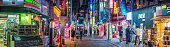 Crowds of shoppers along the pedestrianised streets of Myeong-dong overlooked by the neon lights of stores in the heart of Seoul at night, South Korea's vibrant capital city.
