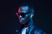 istock Neon portrait of African American man wearing wireless earphones and leather jacket 1153003856