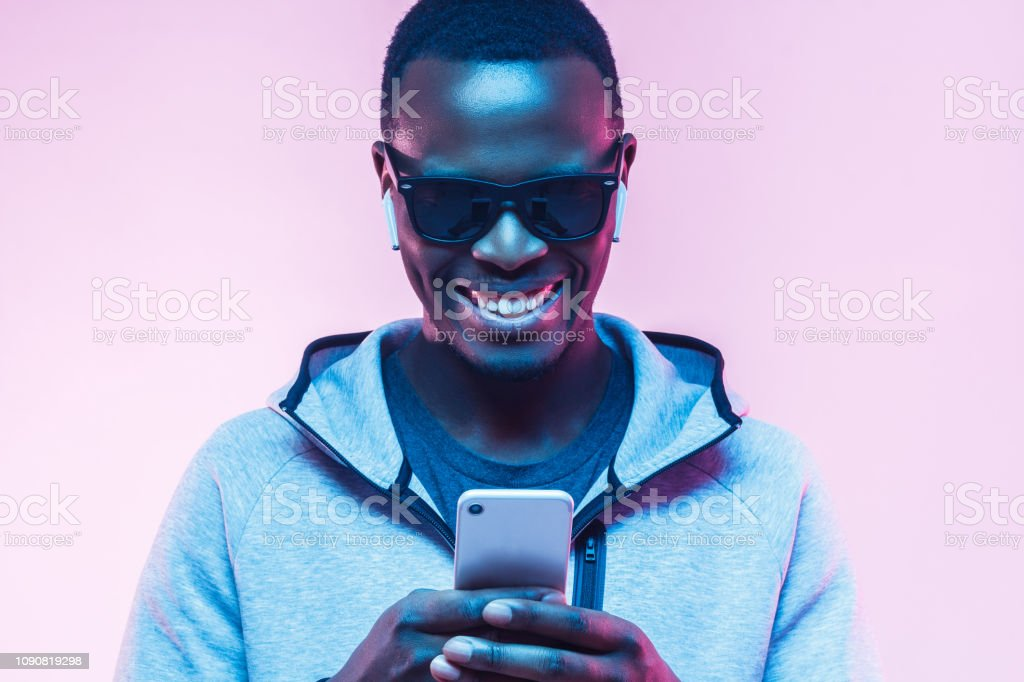 Neon portrait of happy young african man looking at mobile phone