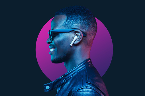 Neon portrait of smiling african american man listening music with earphones, wearing black leather jacket