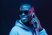 istock Neon portrait of young african man listening music with wireless earphones 1090819268