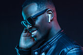 Neon portrait of young smiling african man listening music with earphones, wearing black leather jacket