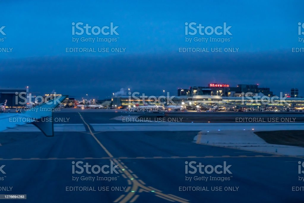 Neon sign of Sheraton Hotel at the terminal of Pearson International airport at dusk, Toronto, Canada Air Canada airplanes parked next to the terminal of Pearson International airport waiting for passengers boarding at dusk, Toronto, Canada. Aerospace Industry Stock Photo