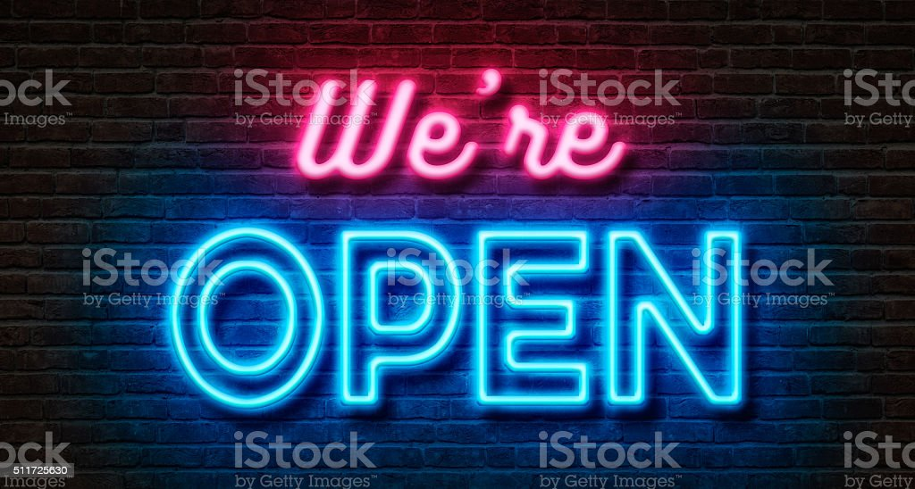 Neon sign on a brick wall - We are open stock photo