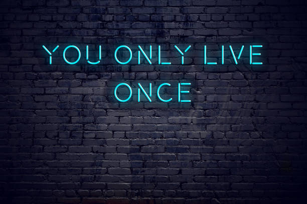 Neon sign with short motivational quote against brick wall stock photo