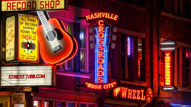 Neon Signs at Night on Broadway Street in Nashville, Tennessee Neon signs lit up at night on Broadway Street in Nashville, Tennessee country and western music stock pictures, royalty-free photos & images