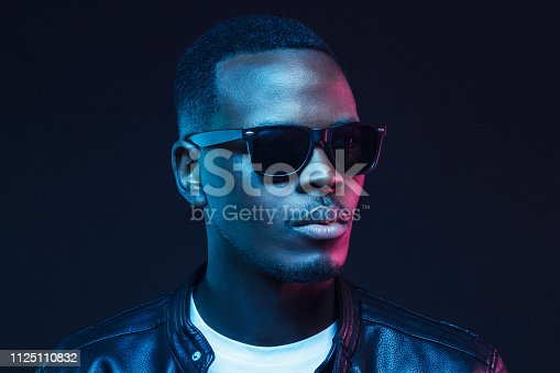 1095939686istockphoto Neon studio portrait of african american male model wearing trendy sunglasses and leather jacket 1125110832