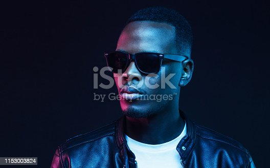 1095939686istockphoto Neon studio portrait of handsome african american male model wearing trendy sunglasses and leather jacket 1153003824