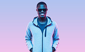 istock Neon studio portrait of handsome african american man wearing sunglasses and hoodie 1285766757