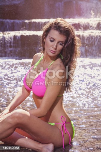Young female adult at a waterfall. Swimwear fashion.