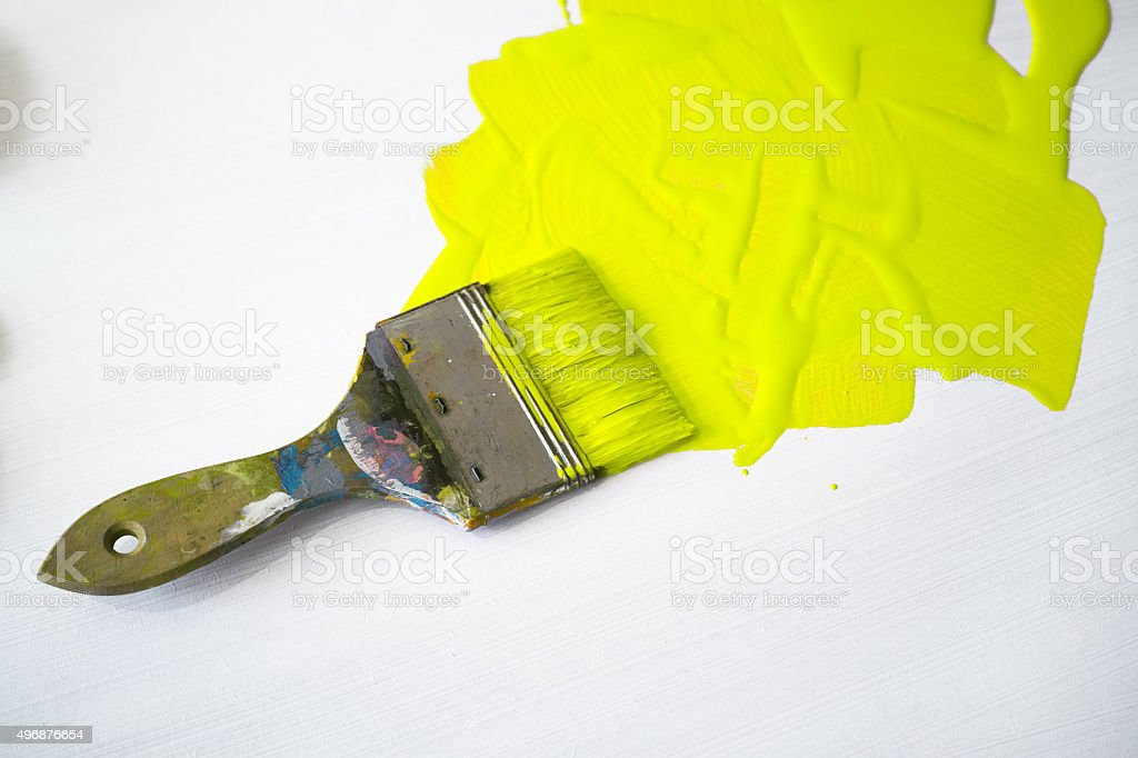 Neon Yellow Paint And Paintbrush With White Background stock photo