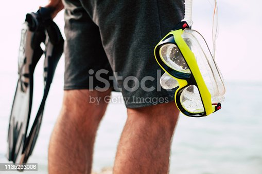 A neon yellow snorkel and grey paddles in the hands of the man wearing black swimming trunks and getting ready to observe the marine life.