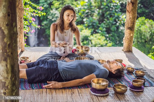 istock Nepal Buddha copper singing bowl at spa salon. Young beautiful man doing massage therapy singing bowls in the Spa against a waterfall. Sound therapy, recreation, meditation, healthy lifestyle and body care concept 1162960269