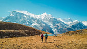 A couple walking towards the Ice lake, as part of the Annapurna Circuit Trek, Himalayas, Nepal. Annapurna chain in the back, covered with snow. Clear weather, dry grass, snowy peaks. High altitude