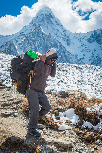 Sherpa porter transporting a heavy load using traditional namlo head band to carry a doko bamboo basket along a rocky trail high in the Khumbu Valley, deep in the Himalaya mountains of the Everest National Park, a UNESCO World Heritage Site, Nepal.
