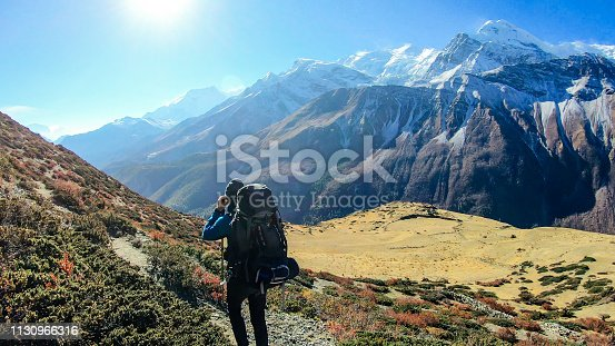 Young man walks on the trail, carries huge backpack, supports himself with sticks, Annapurna Circuit Trek, Nepal. Upper Shreekharka. Below Manang Valley. Dry grass. Other side of the gorge very raw.